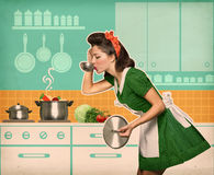 Young housewife testing her soup in the kitchen Royalty Free Stock Images