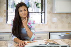 Young housewife thinking of a recipe for dinner Royalty Free Stock Photo