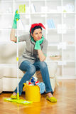 Young housewife is tired of cleaning. Sitting on sofa Royalty Free Stock Images