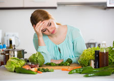 Young housewife tired of cooking vegetables in domestic kitchen Royalty Free Stock Photo
