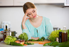 Young housewife tired of cooking vegetables in domestic kitchen Stock Image