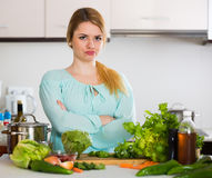 Young housewife tired of cooking vegetables in domestic kitchen Stock Photos
