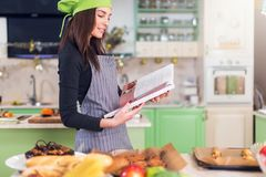 Young housewife trying to find a new recipe in cookbook while standing at table with food and ingredients.  Stock Photo