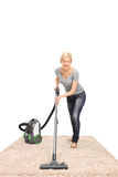 Young housewife vacuuming a carpet Stock Images