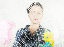 Young housewife washed window with a spray, cloth and detergent. Large glass in foam. Housework concept. Young housewife washed window with a spray, cloth and Stock Photos