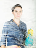 Young housewife washed window with a spray, cloth and detergent. Large glass in foam. Housework concept. Young housewife washed window with a spray, cloth and Stock Photo