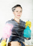 Young housewife washed window with a spray, cloth and detergent. Large glass in foam. Housework concept. Young housewife washed window with a spray, cloth and Stock Images
