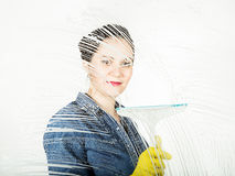 Young housewife washed window with a spray, cloth and detergent. Large glass in foam. Housework concept. Young housewife washed window with a spray, cloth and Royalty Free Stock Photography