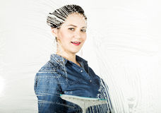 Young housewife washed window with a spray, cloth and detergent. Large glass in foam. Housework concept. Young housewife washed window with a spray, cloth and Stock Photography