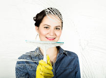 Young housewife washed window with a spray, cloth and detergent. Large glass in foam. Housework concept. Young housewife washed window with a spray, cloth and Royalty Free Stock Image