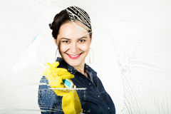 Young housewife washed window with a spray, cloth and detergent. Large glass in foam. Housework concept. Young housewife washed window with a spray, cloth and Royalty Free Stock Photos