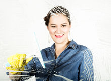 Young housewife washed window with a spray, cloth and detergent. Large glass in foam. Housework concept. Young housewife washed window with a spray, cloth and Royalty Free Stock Images