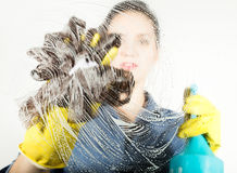 Young housewife washed window with a spray, cloth and detergent. Large glass in foam. Housework concept. Royalty Free Stock Image
