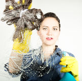 Young housewife washed window with a spray, cloth and detergent. Large glass in foam. Housework concept. Stock Image