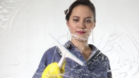 Young housewife washed window with a spray, cloth and detergent. Large glass in foam. Housework concept. stock video footage