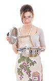 Young housewife wearing apron in the kitchen holding open saucep Stock Photos