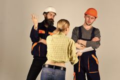Young Housewife Woman Arguing With Male Plumbers, Repairman. Misunderstanding between client and worker. Young Housewife Woman Arguing With Male Plumbers stock image