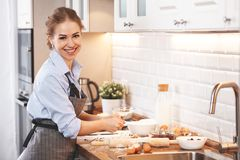 Young woman baking cookies at home in the kitchen. Young housewife woman baking cookies at home in the kitchen Royalty Free Stock Images