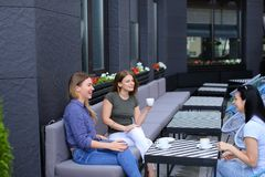 Young housewives meeting at cafe and drinking coffee. Concept of free time and gossips Royalty Free Stock Photography