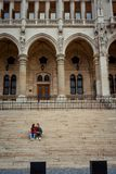 Young hugging couple is holding hands and sitting on the stairs of the old historic building in Budapest, Hungary. Young hugging couple is holding hands and Royalty Free Stock Image
