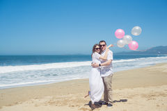 Young hugging romantic couple with balloons on the beach Royalty Free Stock Photo
