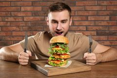 Young hungry man with cutlery eating huge burger royalty free stock images