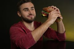 Young hungry man with tasty burger royalty free stock image