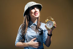 Young hungry woman in pith helmet holding alarm clock stock photos
