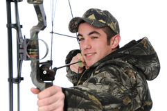Young hunter with bow aiming Royalty Free Stock Image