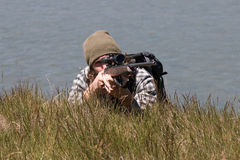 Young hunter with rifle lies on river shore Stock Photos