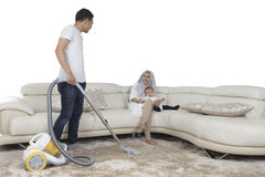 Young husband cleaning mat with vacuum cleaner Stock Image