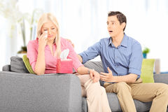 Young husband comforting his sad wife seated on sofa Stock Images
