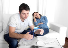 Young husband cutting credit card with scissors woman depressed Royalty Free Stock Photos