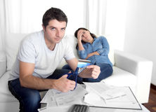 Young husband cutting credit card with scissors woman depressed Stock Photos