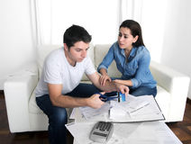 Young husband cutting credit card with scissors woman trying to stop him Royalty Free Stock Photo