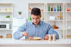 The young husband eating tasteless food at home for lunch Stock Images
