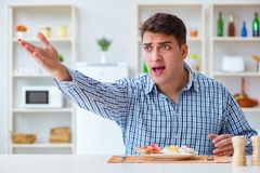 The young husband eating tasteless food at home for lunch Royalty Free Stock Images