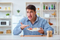 The young husband eating tasteless food at home for lunch Stock Photos
