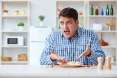 The young husband eating tasteless food at home for lunch Royalty Free Stock Photography