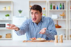 The young husband eating tasteless food at home for lunch Stock Photography