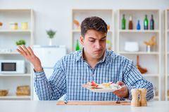 The young husband eating tasteless food at home for lunch Royalty Free Stock Photos