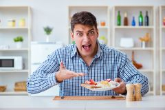 The young husband eating tasteless food at home for lunch Royalty Free Stock Image