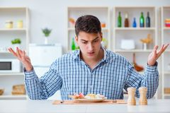 The young husband eating tasteless food at home for lunch Stock Image