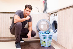The young husband man doing laundry at home Stock Photo