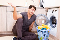 The young husband man doing laundry at home Stock Images