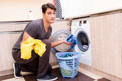 The young husband man doing laundry at home Royalty Free Stock Image