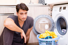 The young husband man doing laundry at home Royalty Free Stock Images