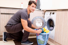 The young husband man doing laundry at home Royalty Free Stock Photos