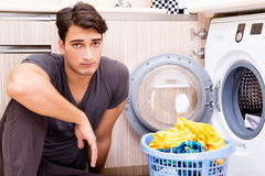 The young husband man doing laundry at home Stock Photography