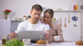 Young husband reading newspaper with wife drinking coffee, morning together. Stock footage stock footage